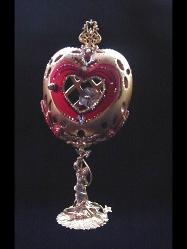 Heart Jewel Eggypiece- Front red heart door opens. Inside, one large drop AB Austrian Crystal and red heart shaped crystal, both resting on a red velvet pillow with gold color details. This piece was imperial gold color and red satin finish. Accented with AB Austrian Crystals and red Ruby crystals. 18K gold plated stand and findings. Decorated box available for this eggypiece.