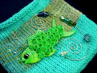 Hand-knitted with silk-wool. Decorated with a handmade Fimo Fish, glass beads and nickel wire. The fish is embellished with Austrian Crystals. Purse hanger is also handmade with nickel and glass beads. Unique design!