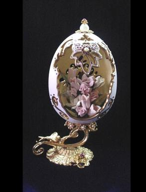Handcrafted and painted in matte satin pink with gold enamel details. Accented w/amethyst Austrian Crystals. Decorated w/porcelain flowers in the inside. 18K gold plated stand and findings. Decorated box available for this eggypiece.