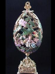 Hummingbird Niche Masterpiece Eggypiece- Hand carved w/extreme care and dedication. Top opens showing the hummingbird in his niche full of porcelain roses. Painted in matte satin pink and green with gold enamel details. Accented w/amethyst and AB Austrian Crystals. Gold glazed 18K gold pigments on the inside. Gold plated heavy stand and findings. Extremely delicate. All-around hand carved. Decorated box available for this eggypiece.